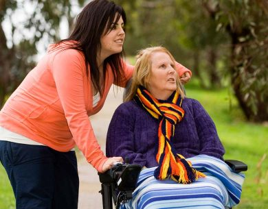 Two women out for a walk, enjoying the sunshine. One woman is in a wheelchair.